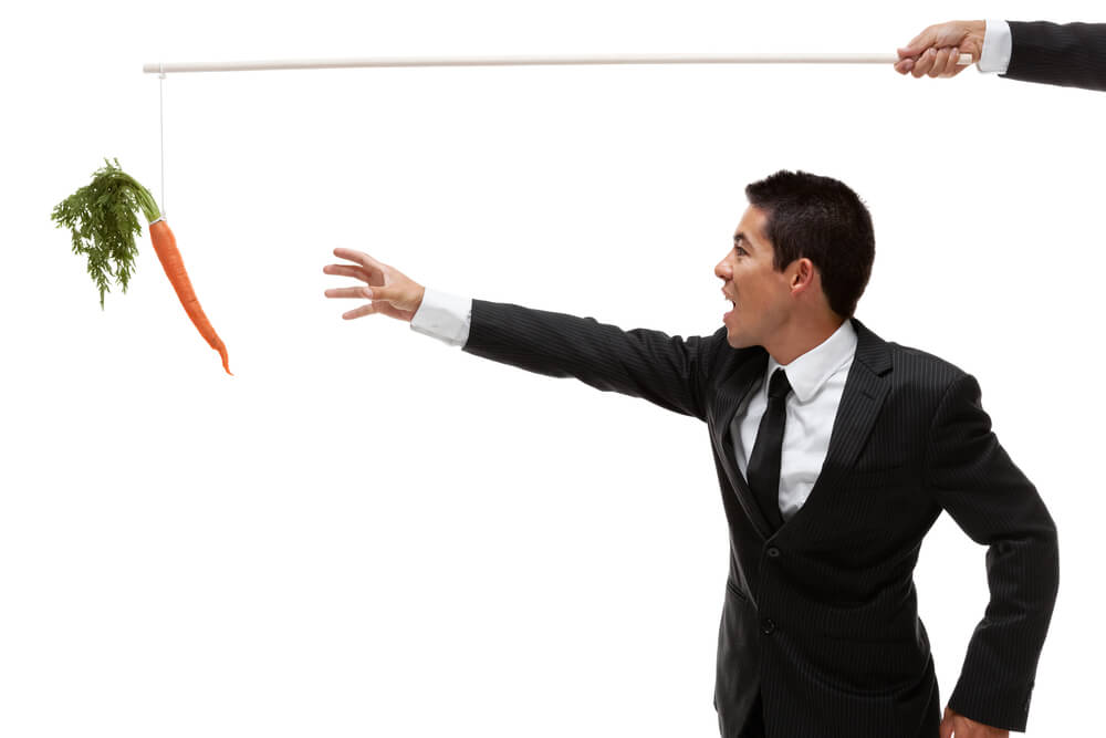 A business man reaches for a carrot at the end of a fishing pole