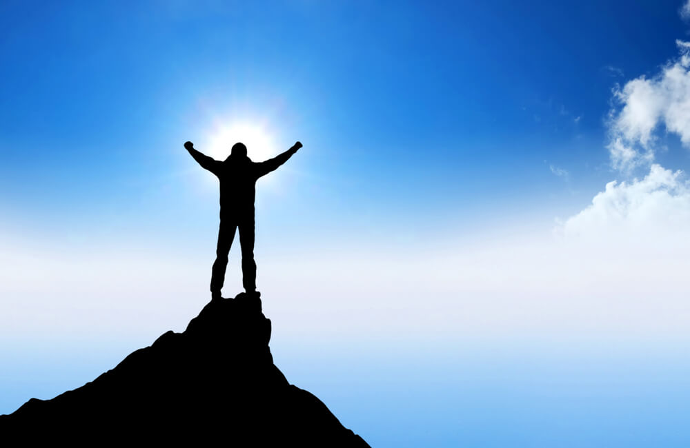 A man has reach the summit of the mountain symbolic of solution selling