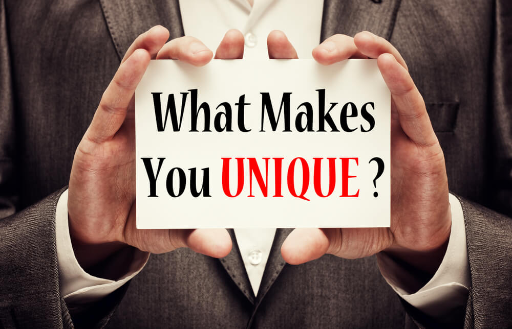 """A man holds a sign saying """"What Makes You Unique"""" illustrating how to be better at solution selling"""
