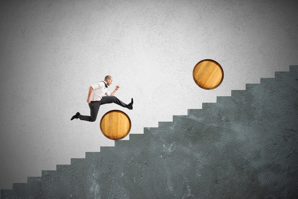a businessman is leaping over barrels to show you need Strategies for Overcoming Sales Objections